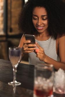 Bom passatempo. linda mulher encaracolada sentada no balcão do bar mandando mensagem de texto para a melhor amiga enquanto toma um coquetel no bar