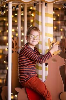 Bom rapaz loiro com óculos no carrossel do ano novo com veados de madeira e luzes brilhantes