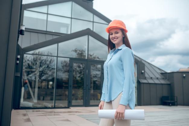 Bom resultado. mulher feliz e brilhante com capacete de segurança laranja com plano de construção perto de um novo edifício moderno com grandes janelas ao ar livre