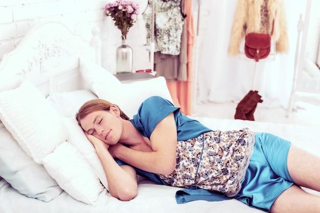 Bom sono profundo. jovem calmo, homossexual coberto de sardas, relaxando em um quarto cheio de roupas e itens femininos
