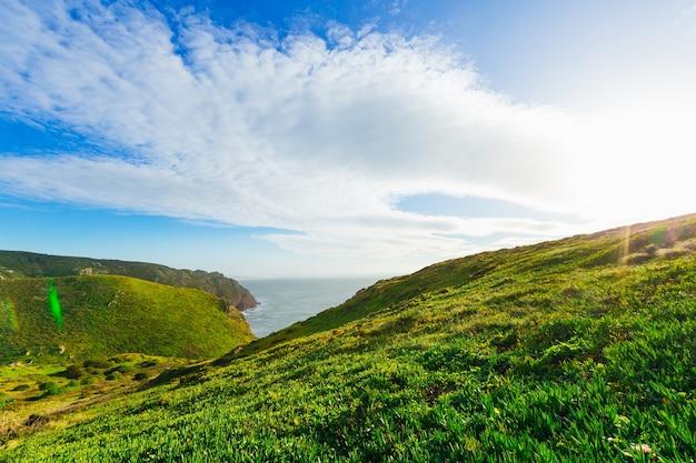 Bom tempo ensolarado sobre colinas verdes e mar calmo