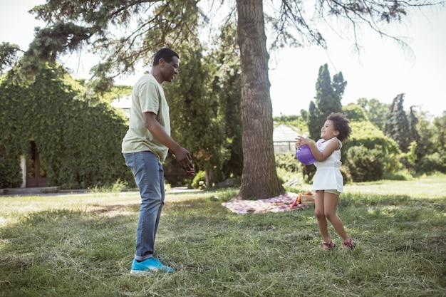 Bom tempo. homem e seu lindo filho jogando bola no parque