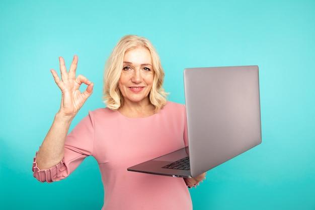 Bom trabalho de laptop. mulher mostrando sinal de ok segurando o computador na sala azul.