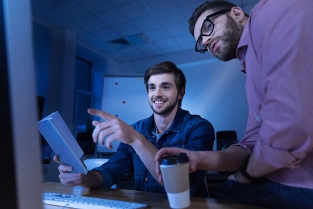 Bom trabalho. homem alegre e positivo, segurando um livro e apontando para a tela do computador enquanto sorri