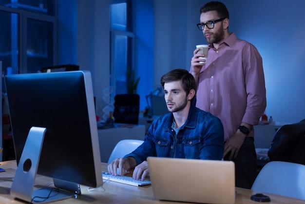 Bom trabalho. homem bonito sério e inteligente parado atrás de seu colega, olhando para a tela do laptop enquanto toma um café