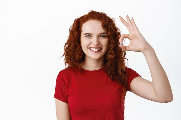 Bom trabalho. menina adolescente ruiva sorridente e confiante mostrando sinal de ok, aprovo e concordo, elogia a excelente escolha e parece satisfeita, em pé com uma camiseta encostada na parede branca