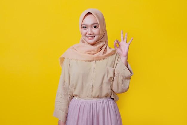 Bom trabalho, orgulhosa mulher jovem asiática feliz usando hijab, mostrando gesto de aprovação piscando alegre isolado em fundo amarelo