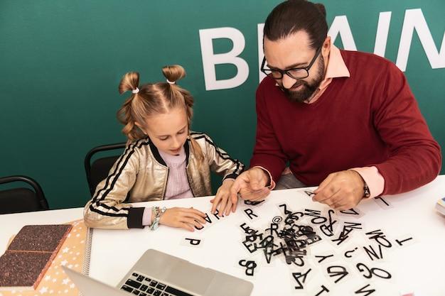 Bom trabalho. professor adulto de cabelos escuros e barbudo usando óculos e parecendo animado enquanto mostra novas palavras para seu aluno
