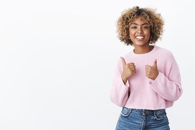 Bom trabalho, resultado legal. retrato de uma mulher afro-americana simpática, atraente e alegre, com cabelo loiro encaracolado e suéter de inverno levantando os polegares em apoio e torcida, como