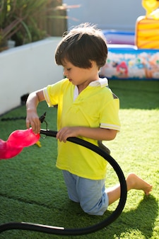 Bomba de criança infla balões na festa de aniversário de uma criança.