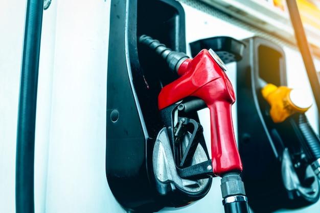 Bomba de gasolina enchendo o bico de combustível no posto de gasolina. máquina dispensadora de combustível.