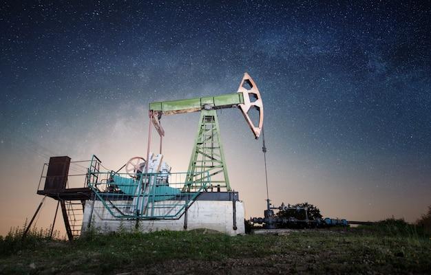 Bomba de óleo no campo de petróleo na noite
