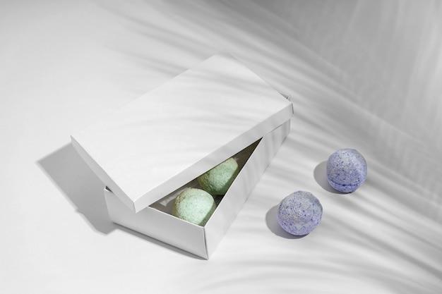 Bombas de banho azuis ao lado de bombas de banho verdes na caixa