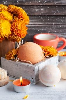 Bombas de banho de aroma em composição de spa com flores de laranja e toalhas. arranjo de aromaterapia, natureza-morta zen com velas acesas