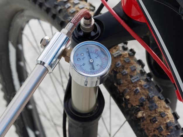 Bombeamento da frente, amortecedor de óleo-ar para bicicleta, usando uma bomba manual especializada.