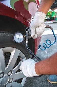 Bombeando pneus de carro em posto de gasolina