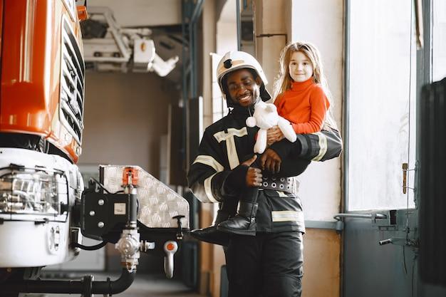 Bombeiro arficano de uniforme. o homem se prepara para trabalhar. cara com criança.