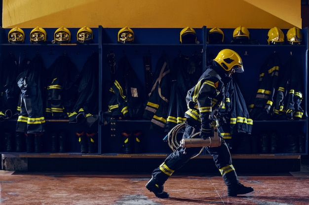 Bombeiro carregando equipamento de incêndio preparado para a ação
