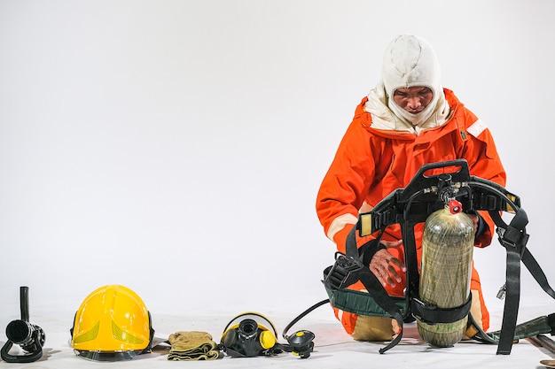 Bombeiro demonstra vestindo uniformes, capacetes e equipamentos diversos para preparar bombeiros em um fundo branco.