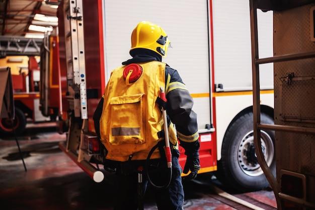 Bombeiro em uniforme de proteção completo em pé no corpo de bombeiros e se preparando para a ação.