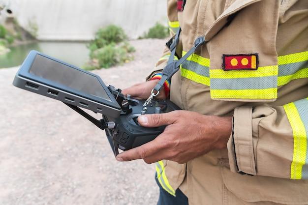 Bombeiro operando drone em busca e salvamento.