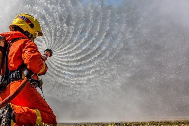 Bombeiro, usando extintor, e, água, de, mangueira, para, combate fogo