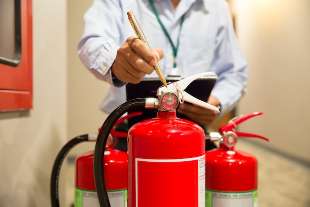 Bombeiro, verificando o tanque de extintores nos conceitos de construção de prevenção de incêndio