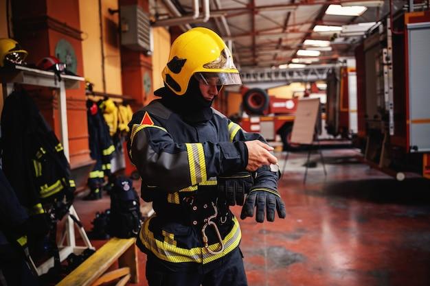 Bombeiro vestindo uniforme de proteção e se preparando para a ação em pé no corpo de bombeiros.