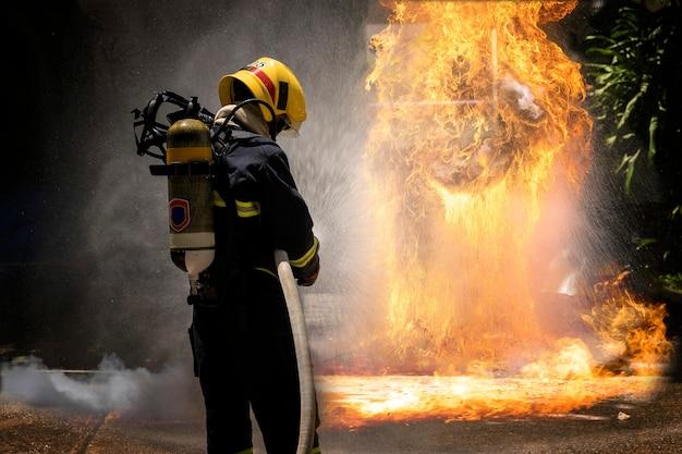 Bombeiros com extintor de pulverização de água de alta pressão para combater a chama de fogo.