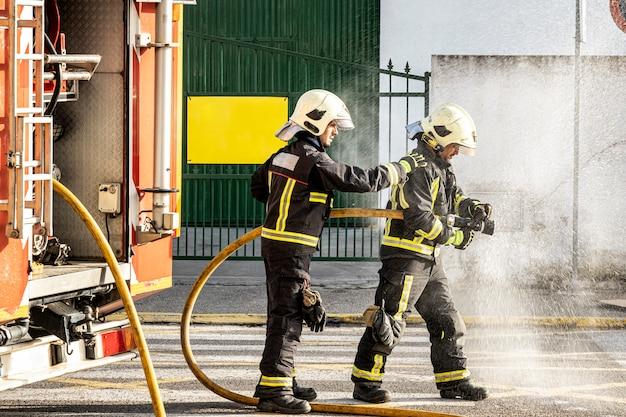 Bombeiros com uma mangueira de água puxando a água para apagar um incêndio