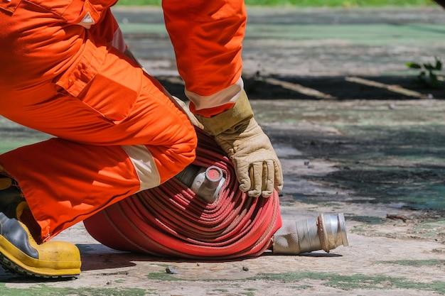 Bombeiros e mangueira de incêndio bobina fogo e escola de treinamento de resgate regularmente para se preparar - ajuda, conceito de proteção contra incêndio