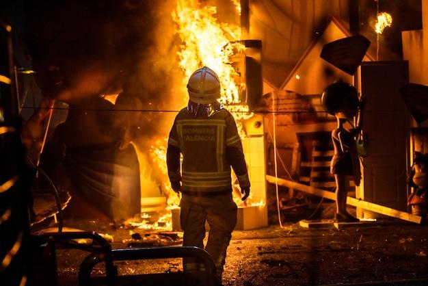 Bombeiros em torno de uma fogueira causada por um falla valenciana controlando as chamas do fogo.