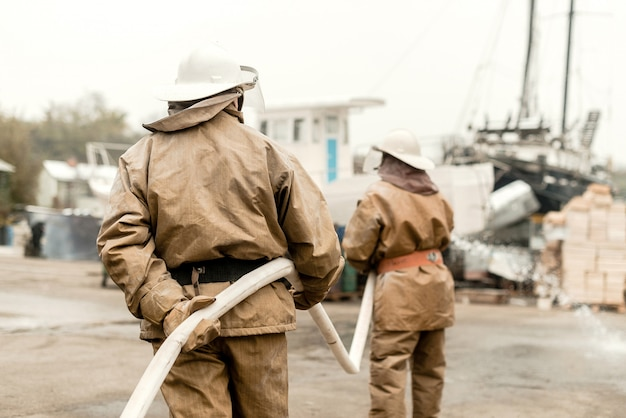 Bombeiros em um porto marítimo usam mangueira em um treinamento