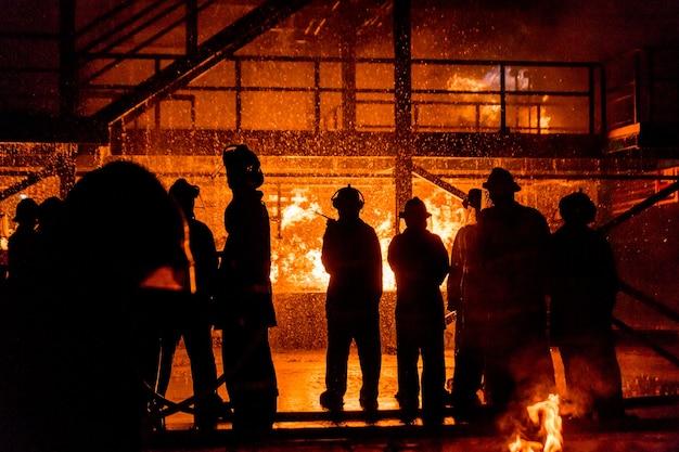 Bombeiros que usam água da mangueira para lutar contra o fogo no treinamento de tiroteio do grupo de seguros