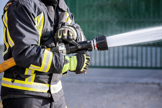 Bombeiros que usam extintores de incêndio e mangueira de água para combater incêndios