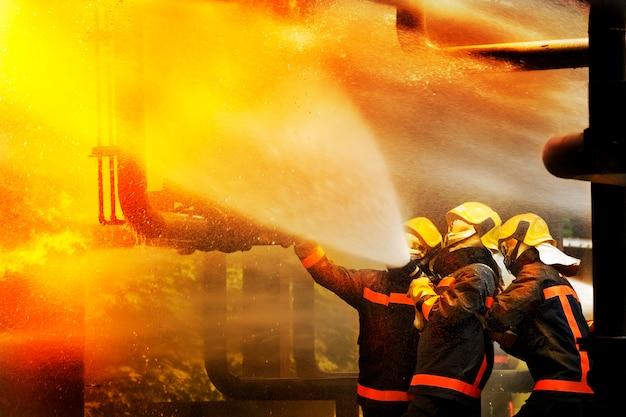 Bombeiros que usam o extintor e a água para o fogo do lutador durante o treinamento do firefight.