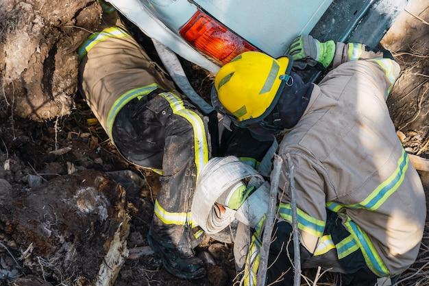 Bombeiros resgatando carro caído na vala.