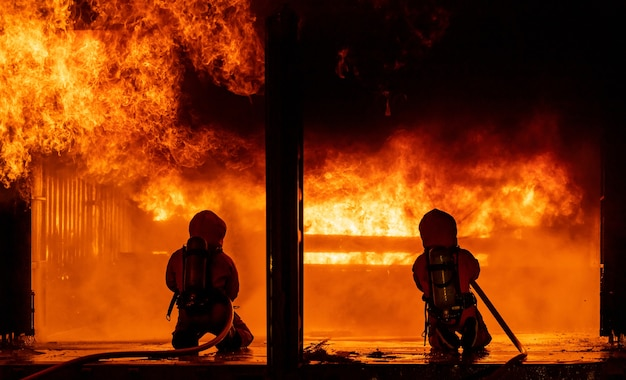 Bombeiros usando extintor de névoa de água para combater a chama de fogo em um grande edifício.