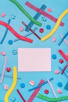 Bombons de açúcar e pirulitos coloridos com envelope no meio