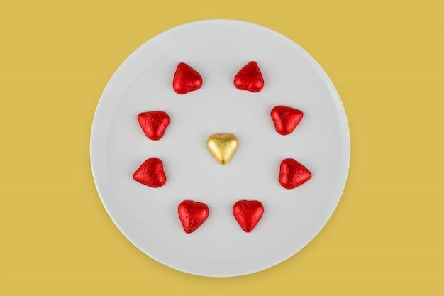 Bombons de chocolate abstratos em forma de coração na chapa branca