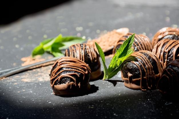 Bombons de chocolate amargo em trufas de chocolate de fundo ensolarado com folhas de hortelã