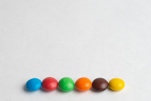 Bombons de chocolate coloridos no fundo branco