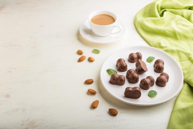 Bombons de chocolate com amêndoas e uma xícara de café sobre uma mesa de madeira branca e têxtil verde. vista lateral, copie o espaço