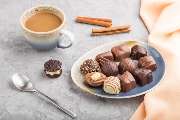 Bombons de chocolate diferentes e uma xícara de café sobre uma mesa de concreto cinza. vista lateral, close up