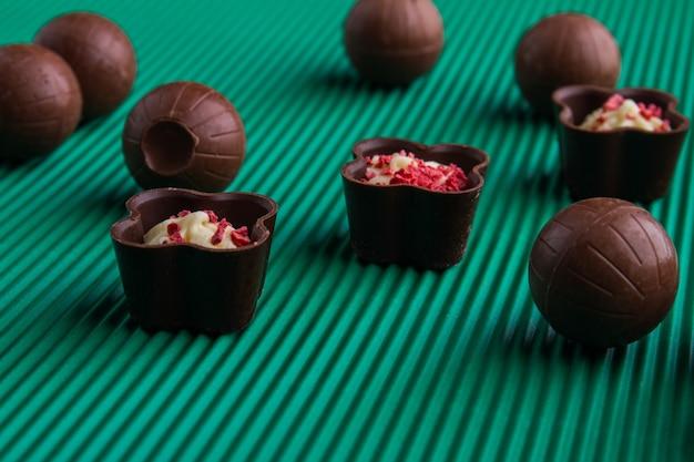 Bombons de chocolate doce marrom close-up sobre fundo verde. conceito de alimentos pouco saudáveis.