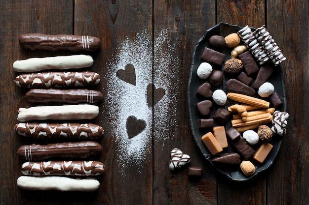 Bombons de chocolate e bolos em madeira escura
