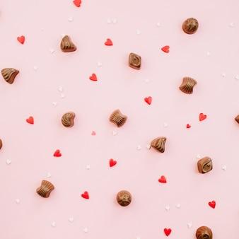 Bombons de chocolate e calores em fundo rosa pálido. camada plana, vista superior