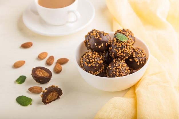 Bombons de chocolate e caramelo com amêndoas e uma xícara de café em uma superfície de madeira branca