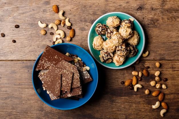 Bombons de chocolate e nozes na madeira