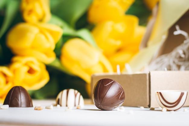 Bombons de chocolate em caixa artesanal e buquê de tulipas amarelas, em superfície de madeira branca